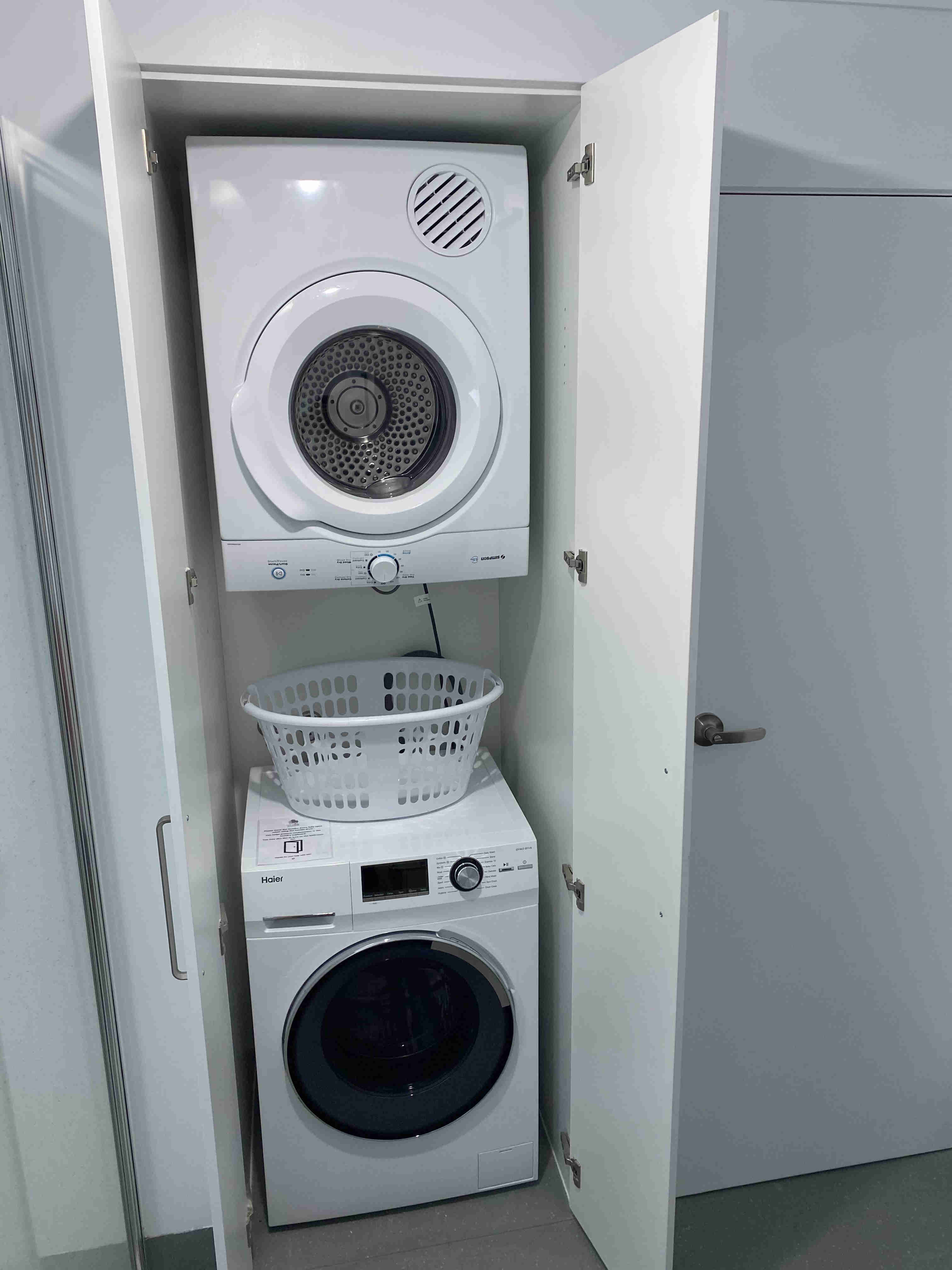 Washing machine, dryer and washing basket in laundry of one bedroom apartments