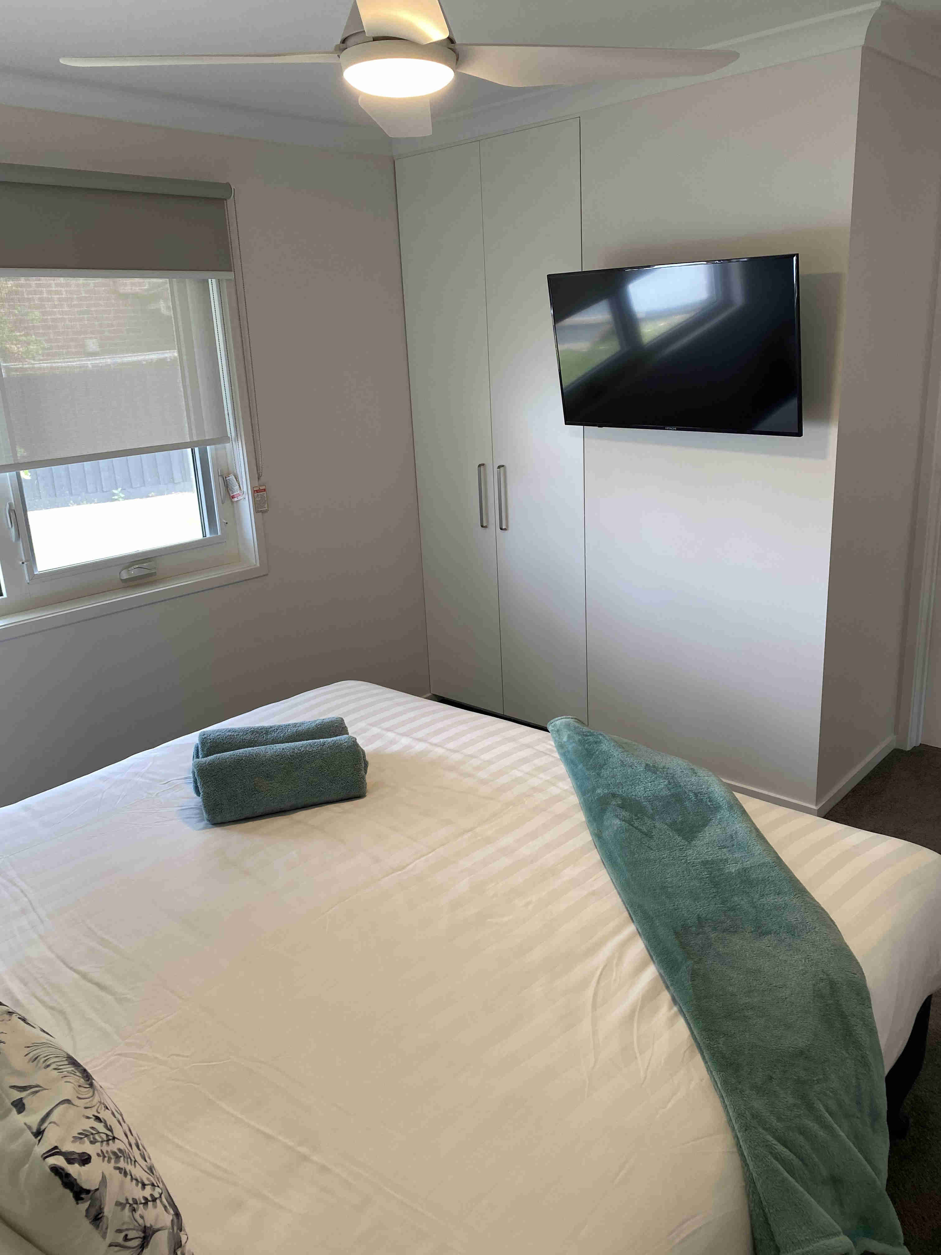 Bed, smart tv and window in one bedroom apartments