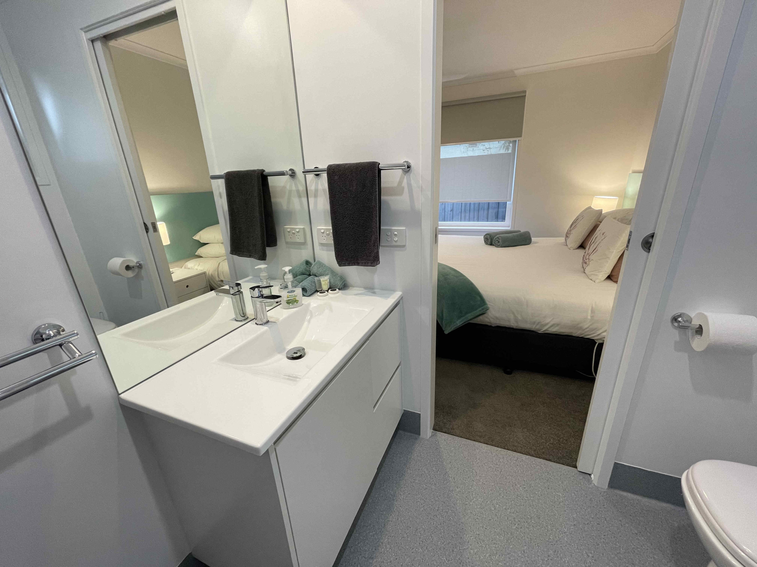 Bathroom vanity of one bedroom apartment with one king bed and one single bed