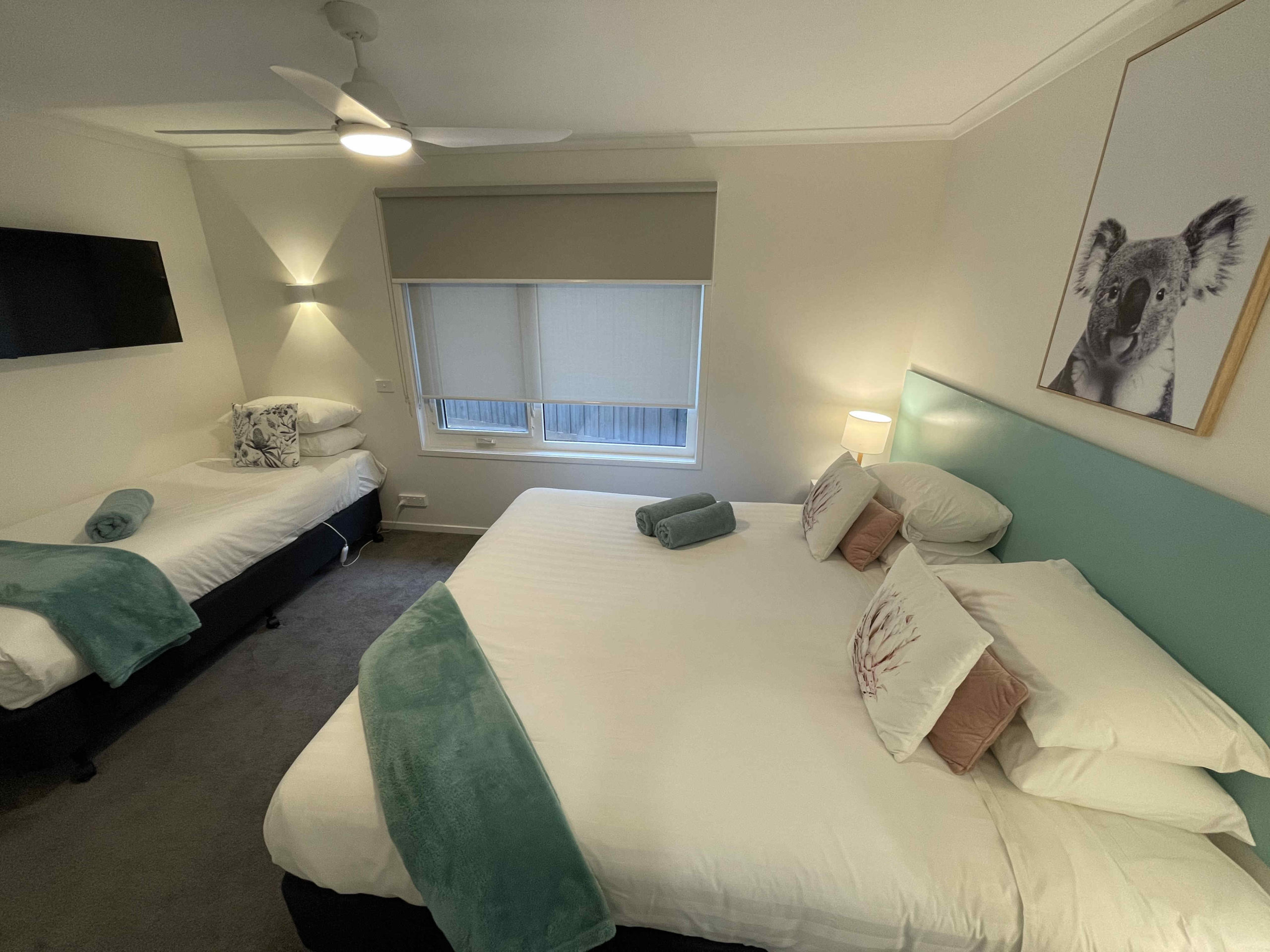 Bedroom of one bedroom apartment with one king bed and one single bed including tv