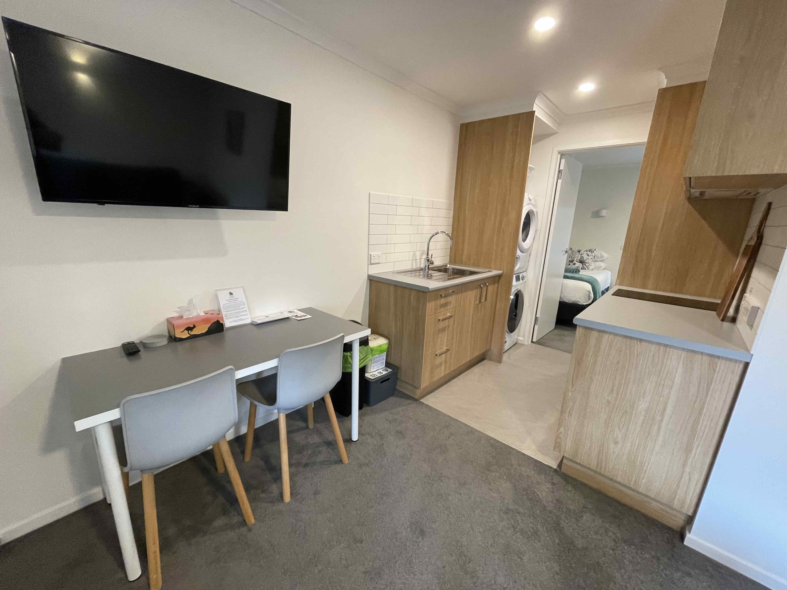 Kitchen and dining area of one bedroom apartment with one king bed and one single bed