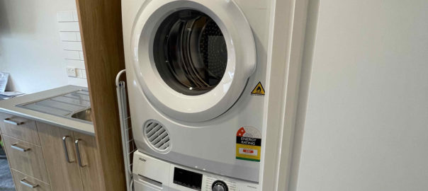 Laundry (washing machine and dryer) in one bedroom apartment with one king bed and one single bed