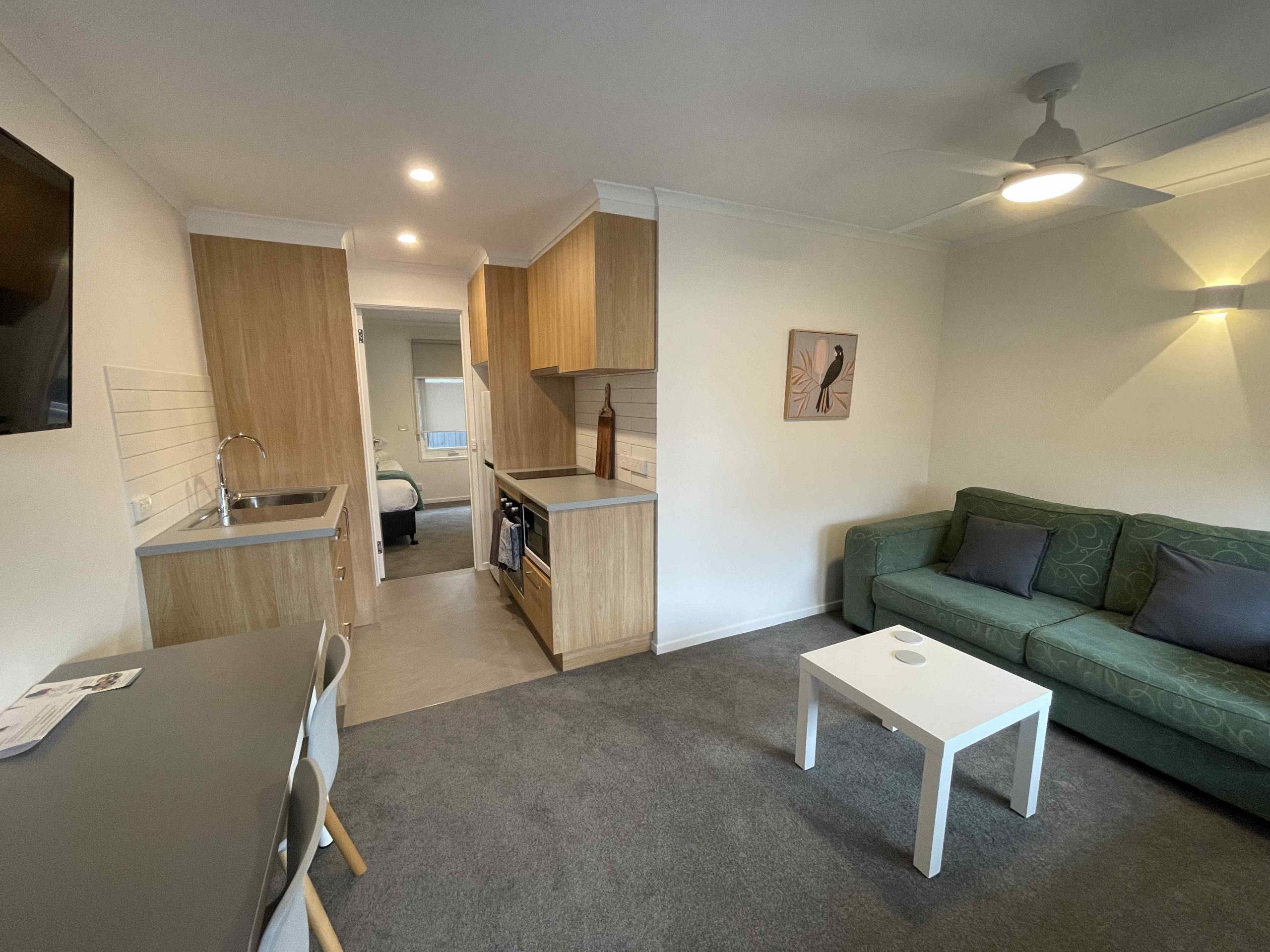 Lounge/living area and kitchen of one bedroom apartment with one king bed and one single bed